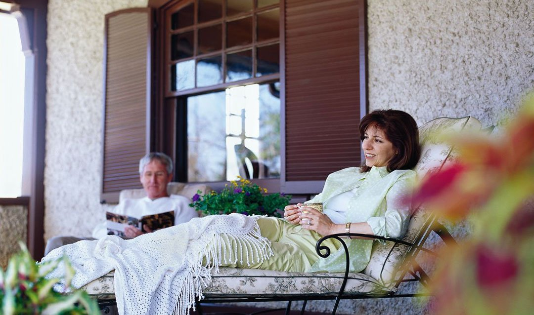 Guests relaxing on the porch of a private oasis--the Market Gardener's Cottage on Biltmore Estate