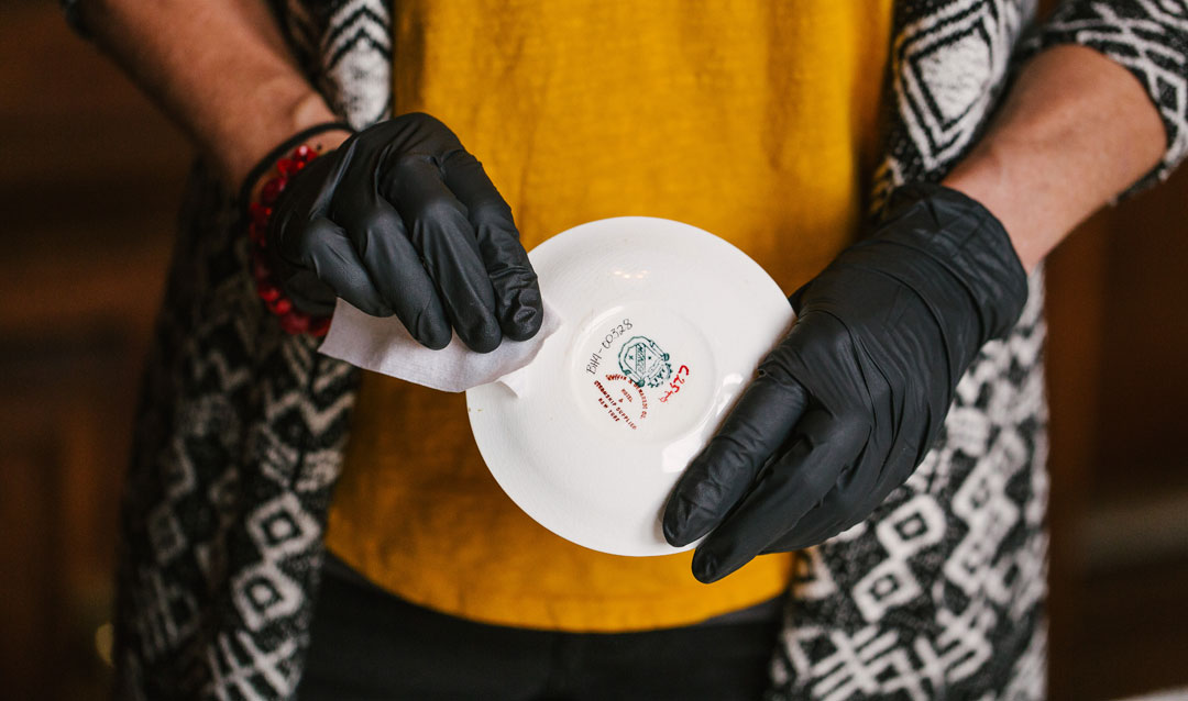Biltmore conservator shows manufacturer's mark on the bottom of a china saucer