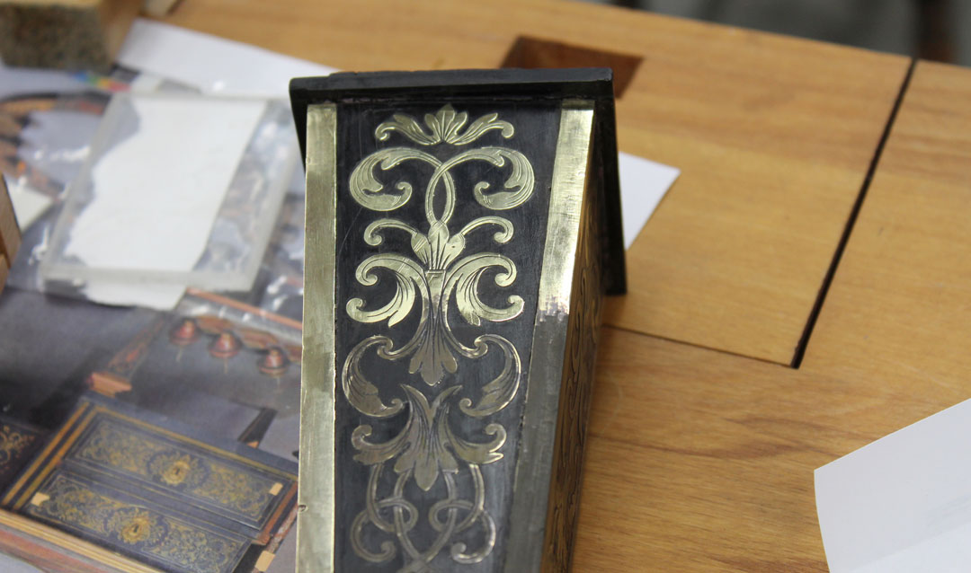 A decorative desk leg showing old and new brass marquetry