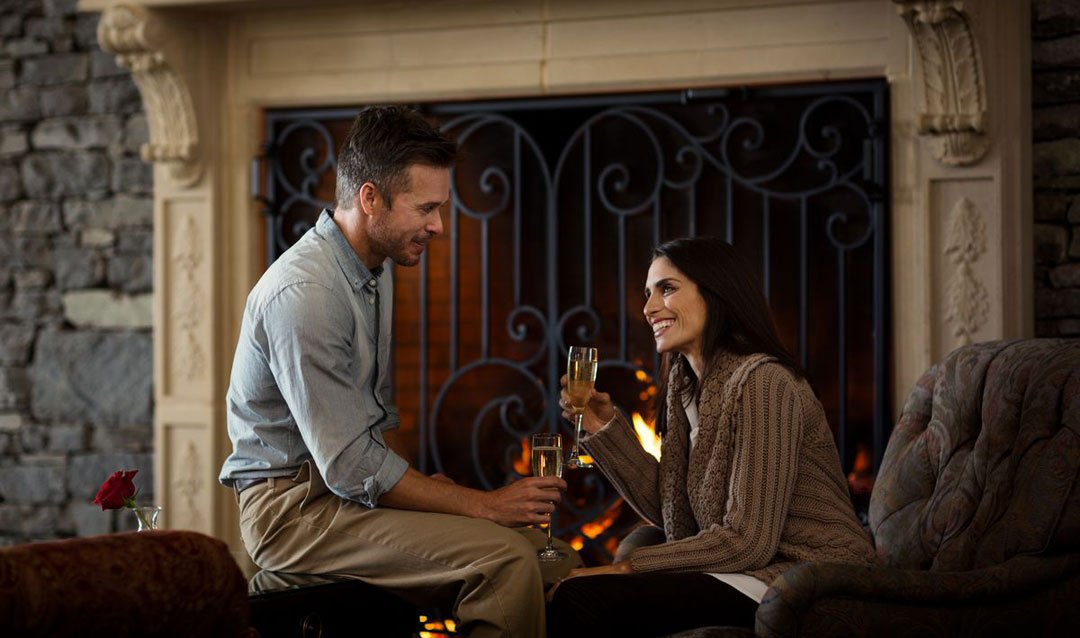 Couple with sparkling wine by a fireplace