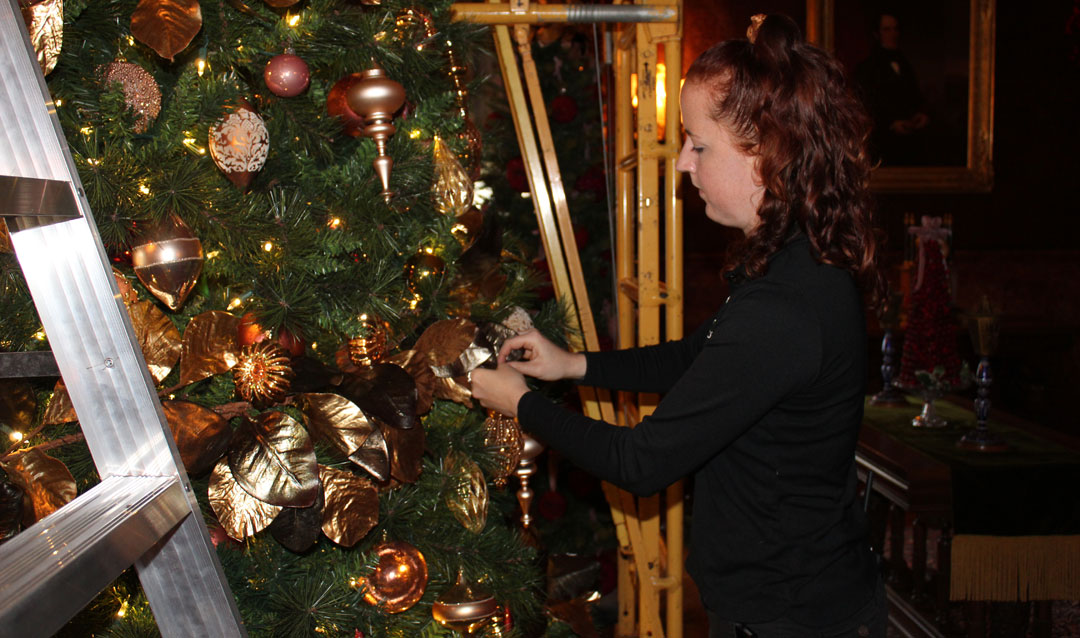 Adding ornaments to a Christmas tree in the Breakfast Room