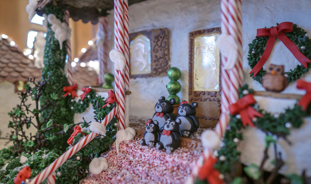 A family of bears on the steps of the gingerbread cottage