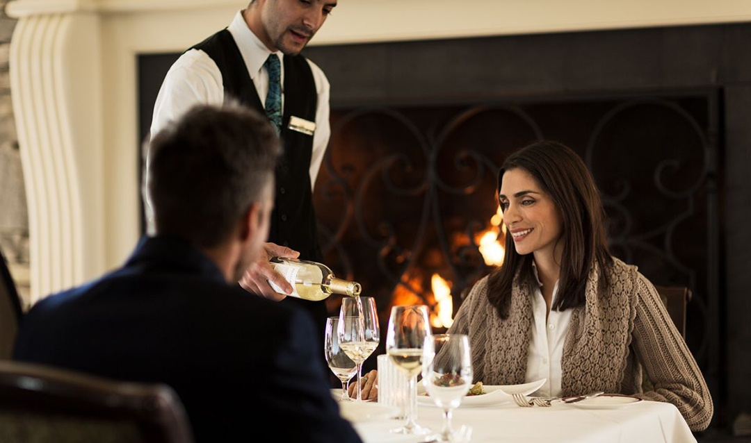 Couple dining by fireplace