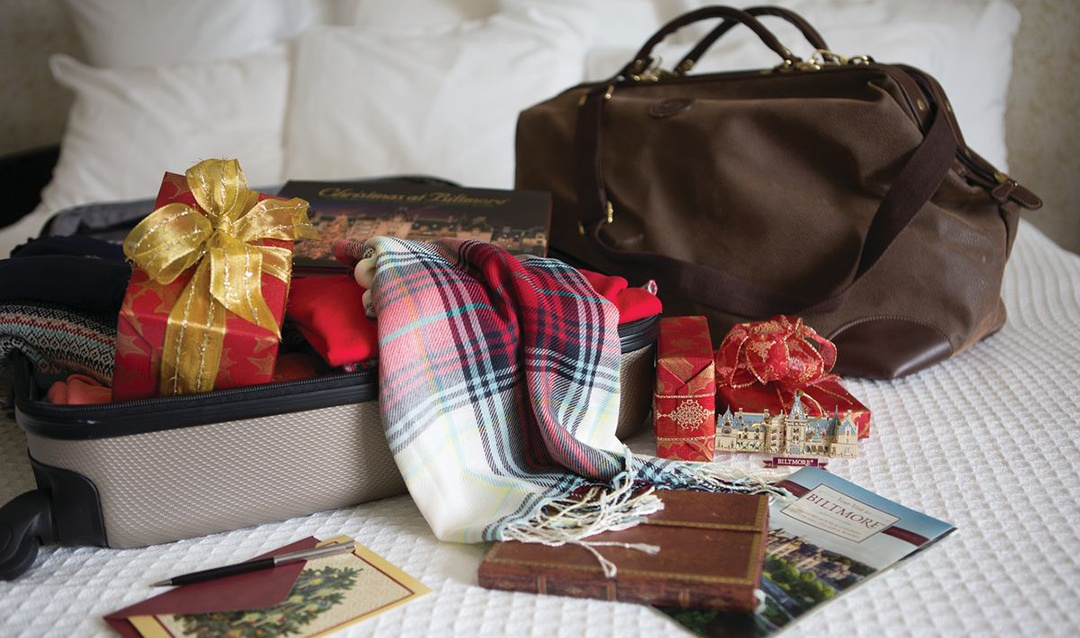Luggage and christmas gift on bed