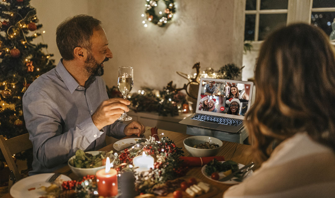 Couple video chatting with friends during Christmas dinner