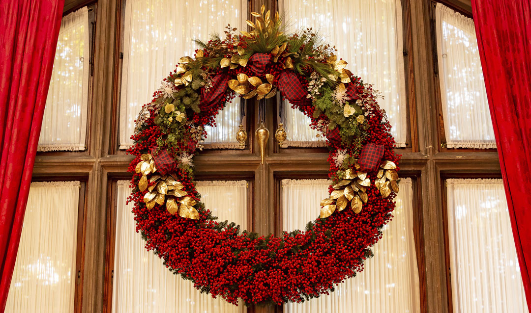 Enornous red berry wreath in the Library at Biltmore House