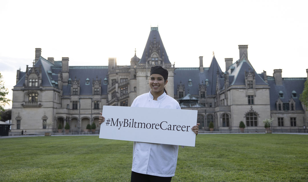 Culinary staff holds career sign in front of Biltmore House