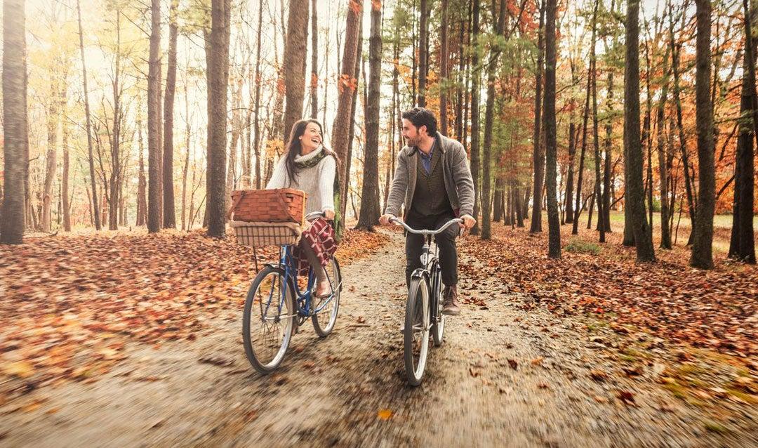 Couple biking through fall leaves